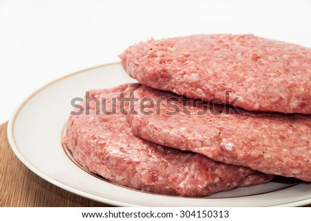 Three raw burgers on the plate ready for frying.