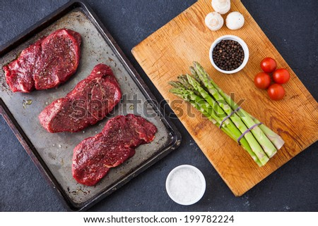 Three raw fillet steaks with green asparagus, mushrooms, cherry tomatoes, salt and pepper, on a wooden board with a slate background. Shallow depth of field.