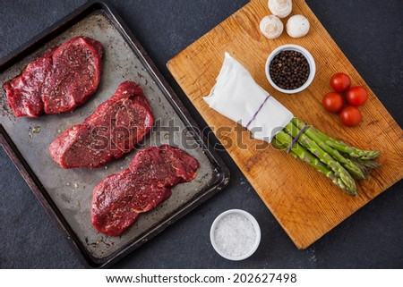 Three raw fillet steaks with green asparagus, mushrooms, cherry tomatoes with a slate background