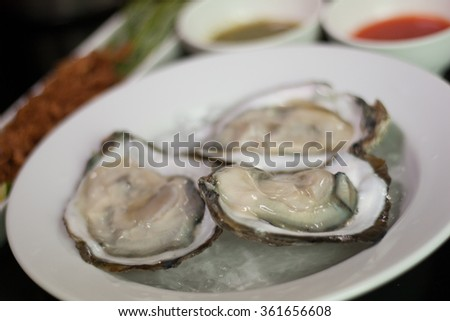 Three Raw Oysters with Thai Sauce in Background