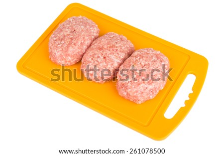 Three raw pork cutlet on plastic board isolated on white background