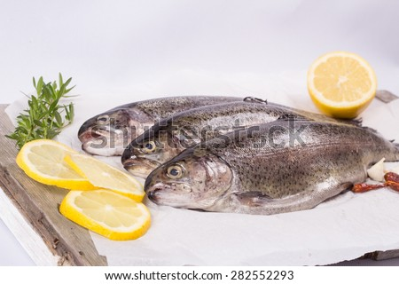 Three raw trouts on paper with thyme and lemon  on a rustic wooden table