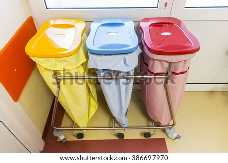 Three recycle bins in a hospital for different kinds of waste.