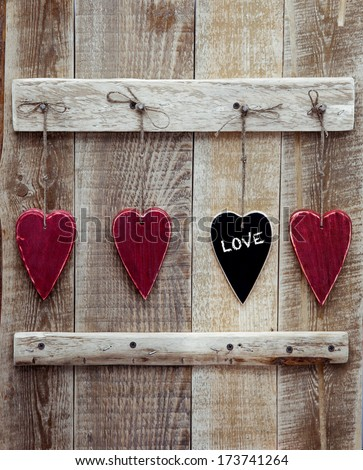 Three  red and one black chalk heart with the word Love hanging on the wooden weathered rustic background - stock photo