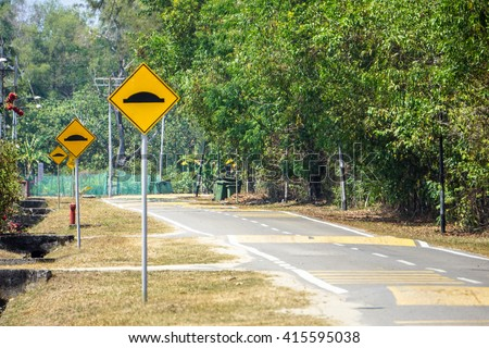Three red and yellow triangular warning road sign a warning of a bumpy road ahead.  - stock photo