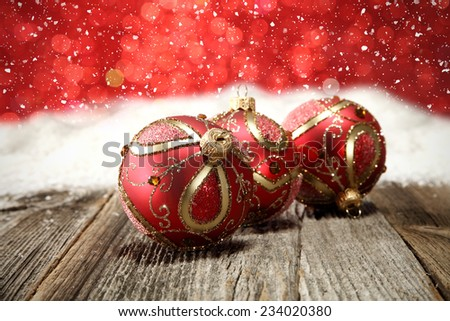 three red balls of xmas time and wooden old table of snow and red wall space