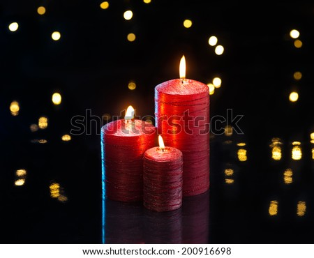 Three red candles in front of dark background - stock photo