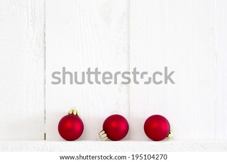 Three red christmas balls on white wooden background. - stock photo