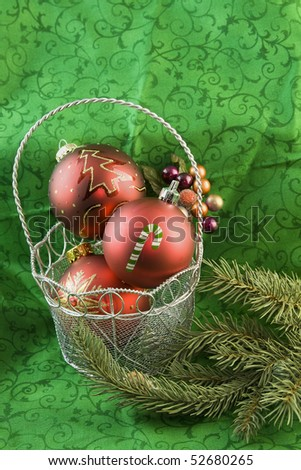 three red, Christmas ornaments in a silver basket - stock photo