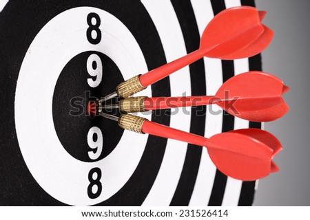 Three red darts in the target center on gray background. - stock photo