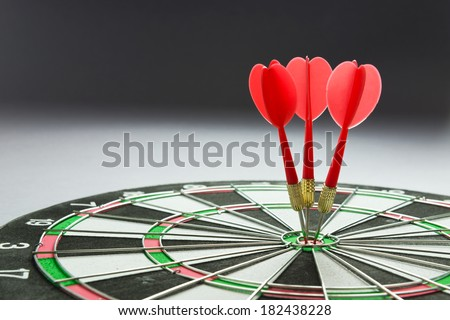 Three red darts pinned right on the center of dartboard - stock photo