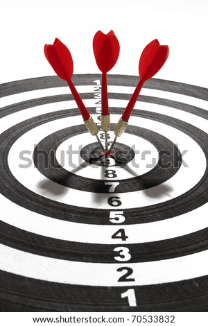 three red darts smack in the center of the board - stock photo