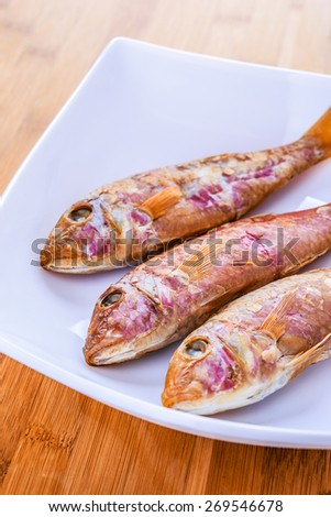 Three red fishes lie on white plate. - stock photo