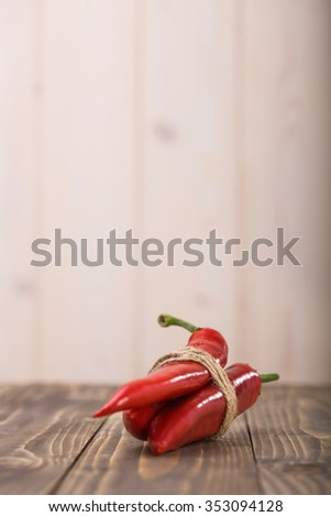 Three red fresh eating raw pod peppers cayenne vegetable tied by twine laying on wooden table on light background fiery seasoning for mexican food indoor copyspace closeup, vertical picture - stock photo
