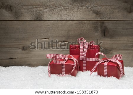 Three red gifts for christmas on a wooden background with snow for a greeting card - stock photo