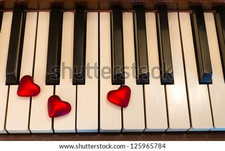 Three red hearts adorn piano keys. - stock photo