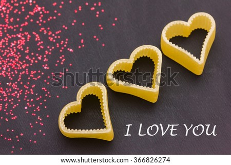 three red hearts and glitters on a blackboard - stock photo