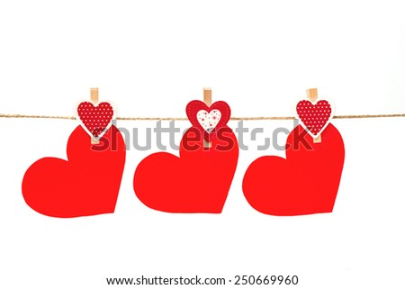 Three red hearts hanging on twine on isolated background for valentines day - stock photo