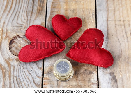 Three red hearts made by hand next to some coins on an old wooden table
