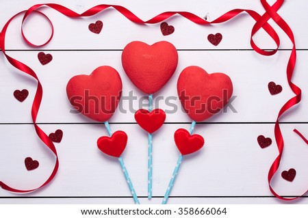 Three red hearts on a white wooden background.Red ribbon and little hearts.