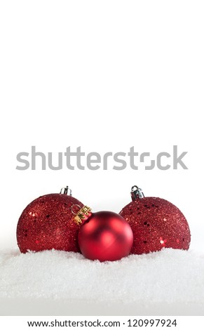 Three red ornaments in snow on white background - stock photo