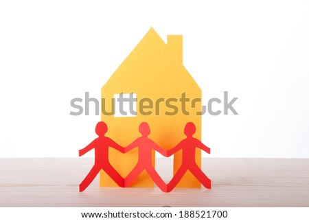 Three Red People in front of a yellow House, out of Paper - stock photo