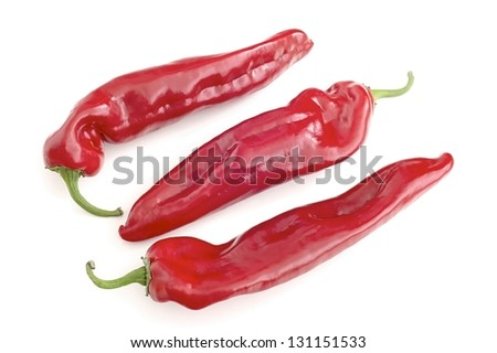 three red peppers on a white background
