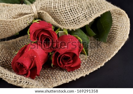 Three red roses and burlap on black background - stock photo