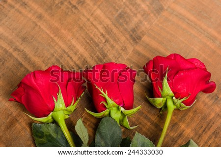 Three red roses laid on a rough wooden table - stock photo
