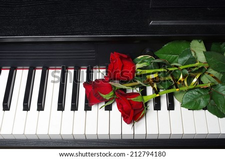 Three red roses on a piano keyboard