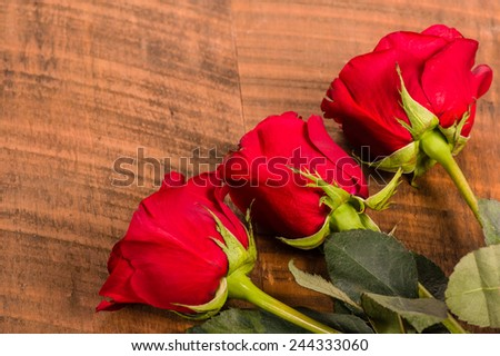 Three red roses on a rough wooden table - stock photo