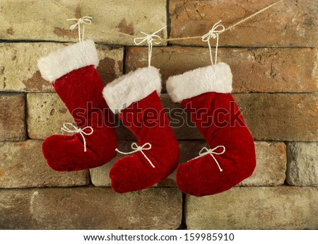 Three red Santa boots on chimney place background - stock photo