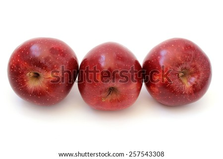 Three red shiny ripe apples are inclined - stock photo
