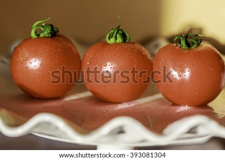 three red shiny tomatoes on a Decorated white Dish