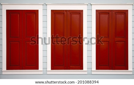 Three red storm shutters closed to protect from the weather - stock photo