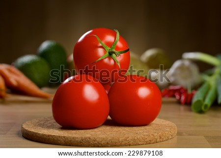 Three red tomatoes on the wooden table with different vegetables on the background - stock photo