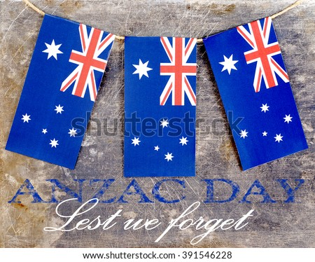 Three red, white and blue Australian flags suspended from a twine rope in front of a grungy, steel background for Anzac Day (Australian and New Zealand Army Corps) in Australia on April 25. Text added - stock photo