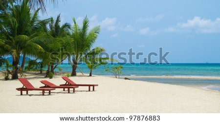 Three red wooden beach chairs on white sand against blue ocean with coconut palm trees  background.