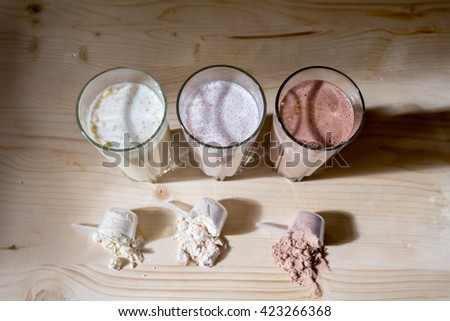 Three resh milk, chocolate, blueberry and banana drinks on table near three scoop - stock photo