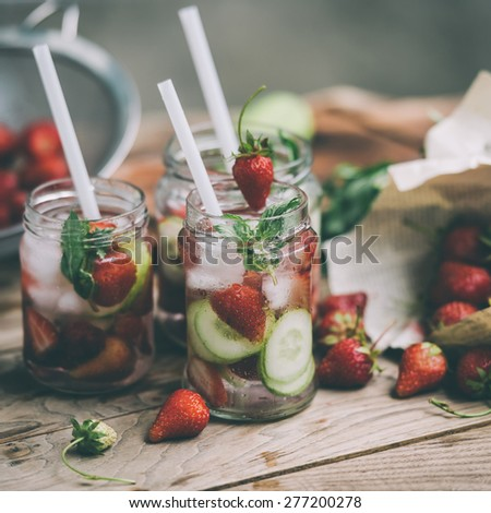 Three retro glass jars of lemonade with  strawberries, cucumber and mint on wooden table. Toned image - stock photo
