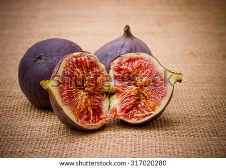 Three ripe figs from jute background, close up - stock photo
