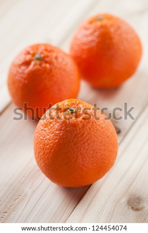 Three ripe mandarins on wooden boards, studio shot