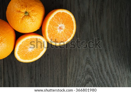 three ripe oranges on wooden table one half cut shot from above - stock photo