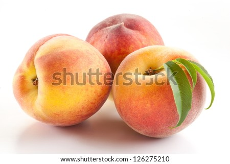 Three ripe peach with leaves on white background. - stock photo