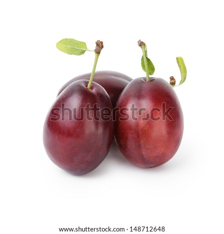 three ripe plums with leaves, isolated on white