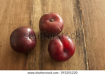Three ripe red juicy home grown plums on an old wooden table with copy space - stock photo