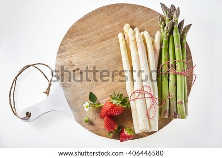 Three ripe red strawberries with stem along side of bundled white and green asparagus on wooden tray - stock photo