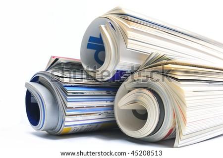 Three rolled magazines over white - stock photo