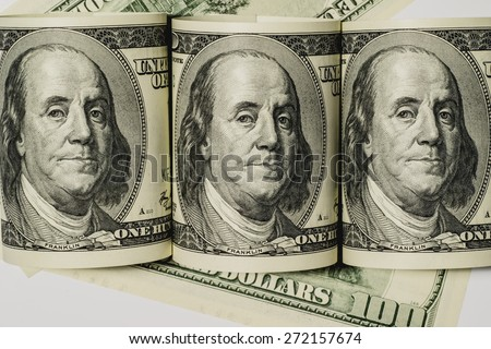 Three rolled up one hundred dollar bills on a white background - stock photo