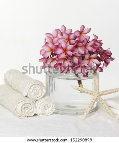 Three roller towel with frangipani in water bowl with starfish  - stock photo